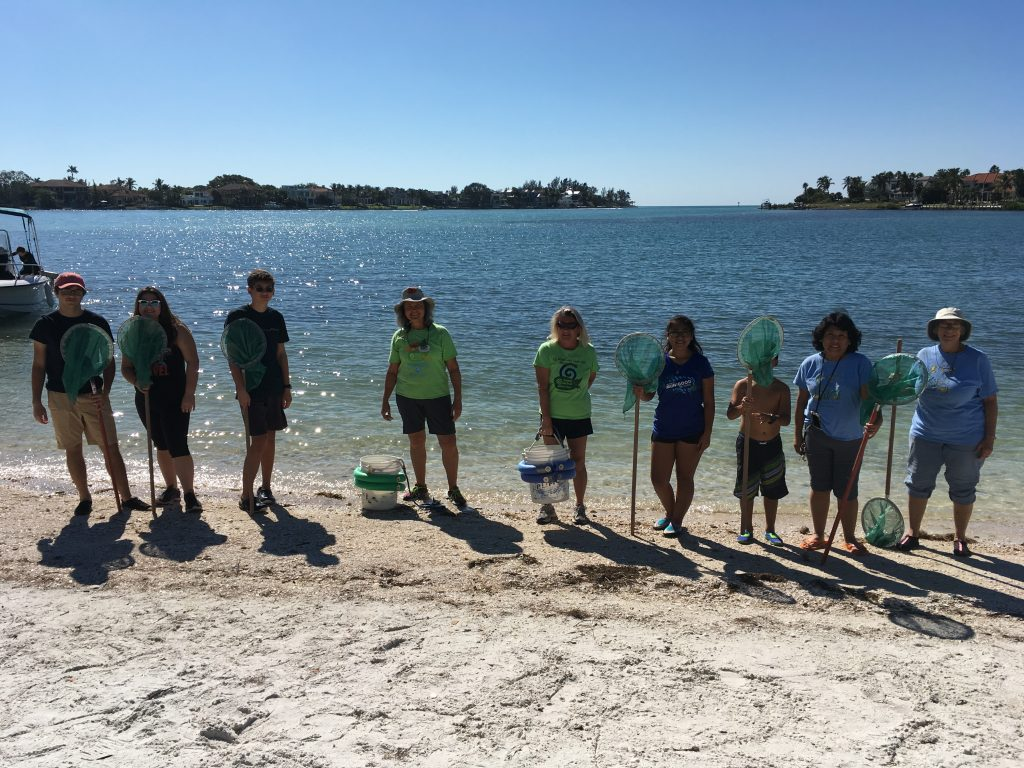 Volunteers holding nets in front of Sarasota Bay