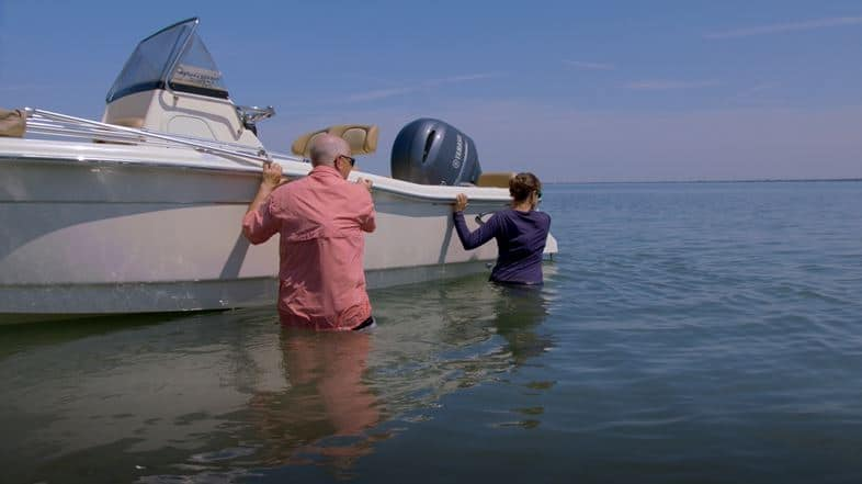 Two people standing in water pushing a boat