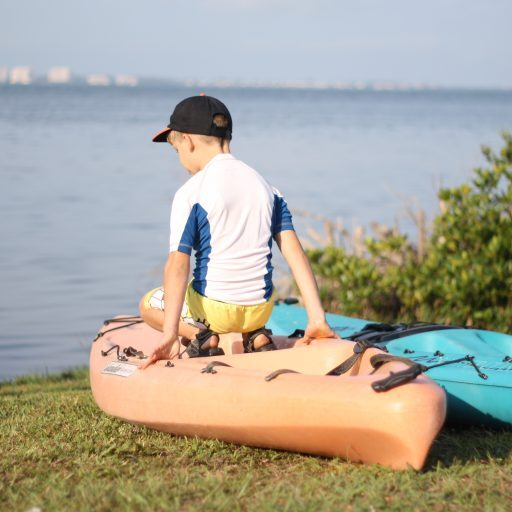 young boy sitting on his kayak facing water